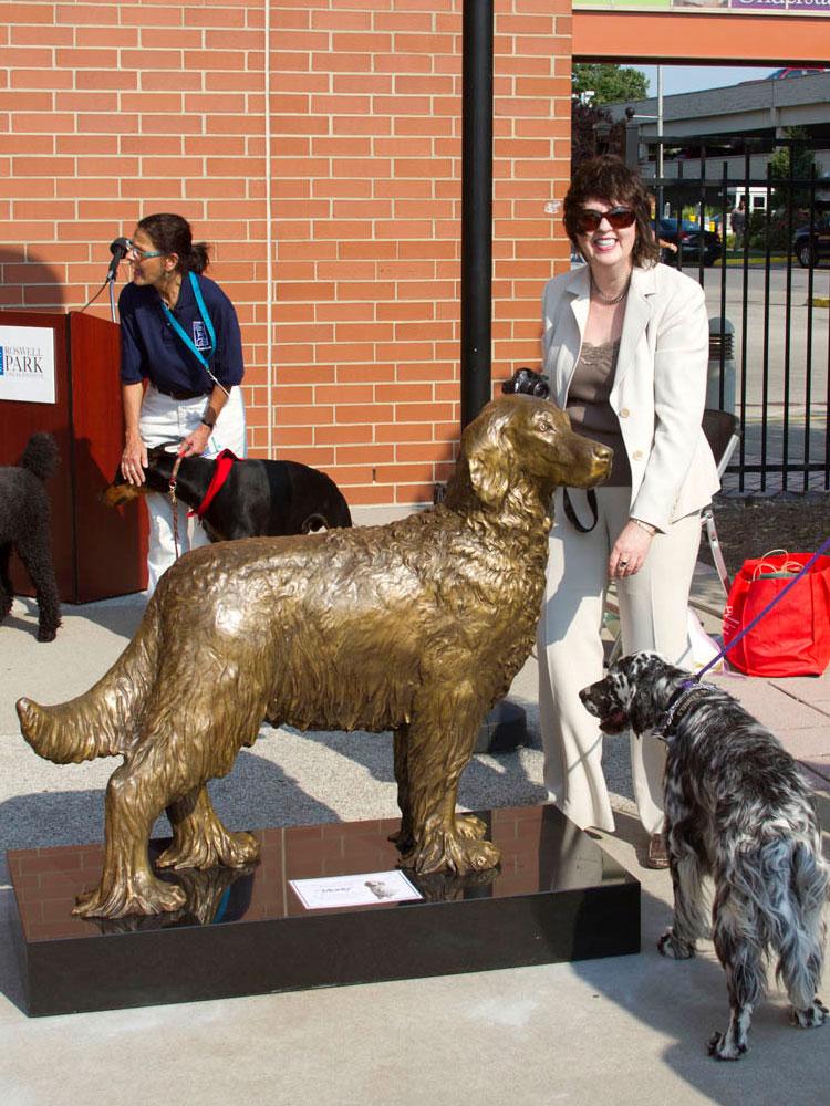 Sculptor Lena Toritch with bronze portrait statue of Monty